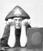 "Aleister Crowley in A.'.A.'. regalia making the sign ""Vir."""