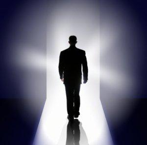male silhouette walking towards the light